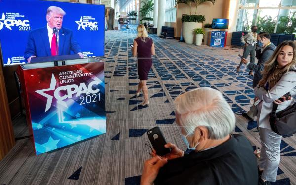 Personas observan el discurso del expresidente de EE.UU. Donald J. Trump en la clausura de la Conferencia de Acción Política Conservadora, este 28 de febrero de 2021, en Orlando (Florida