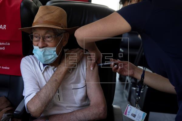 Una enfermera vacuna contra la covid-19 a un adulto mayor, en un puesto de vacunación móvil diseñado para descongestionar los centros de salud, en la comuna de La Reina, en Santiago (Chile).