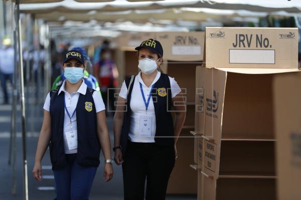 Dos miembros de la Fiscalía General son vistas en un colegio electoral antes de la entrada de ciudadanos que esperan votar los 84 escaños de la Asamblea Legislativa y las 262 alcaldías, hoy en San Salvador (El Salvador)